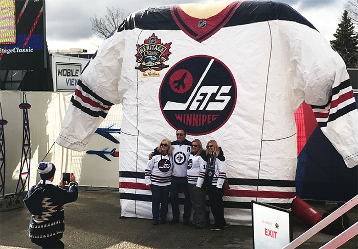 Fans pose in front of a giant Winnipeg Jets jersey at the NHL Heritage Classic 2016 Spectator Plaza in Winnipeg.